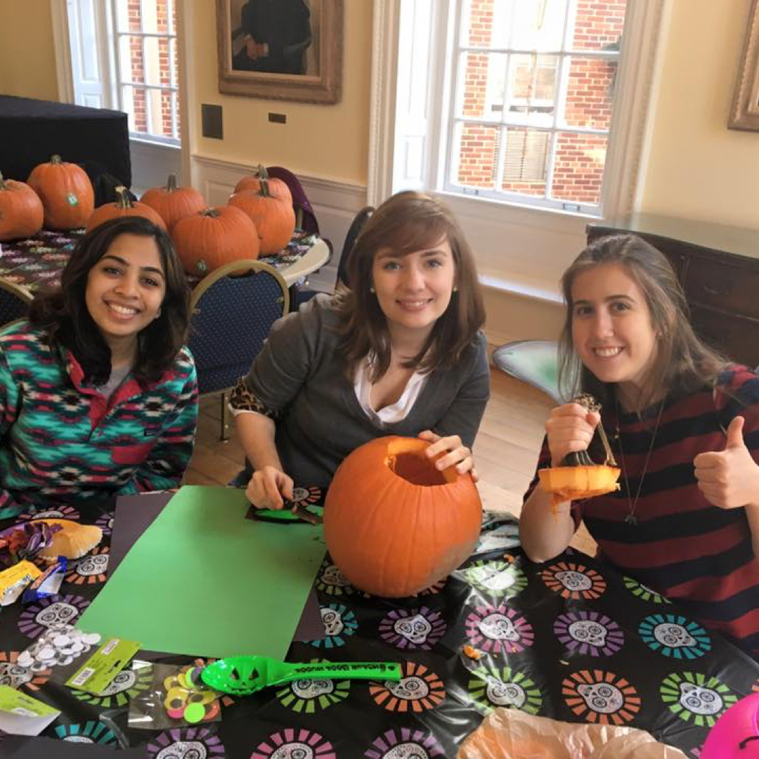 Three students carving pumpkins
