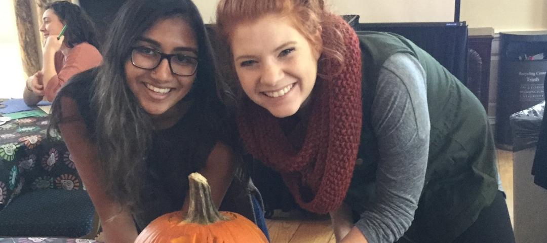 2 smiling girls with a pumpkin